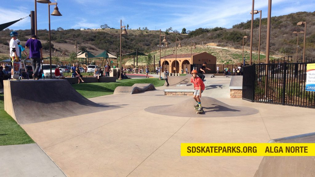 A skateboarder in a red shirt getting speed over a pump bump at Alga Norte skate park in Carlsbad, San Diego.